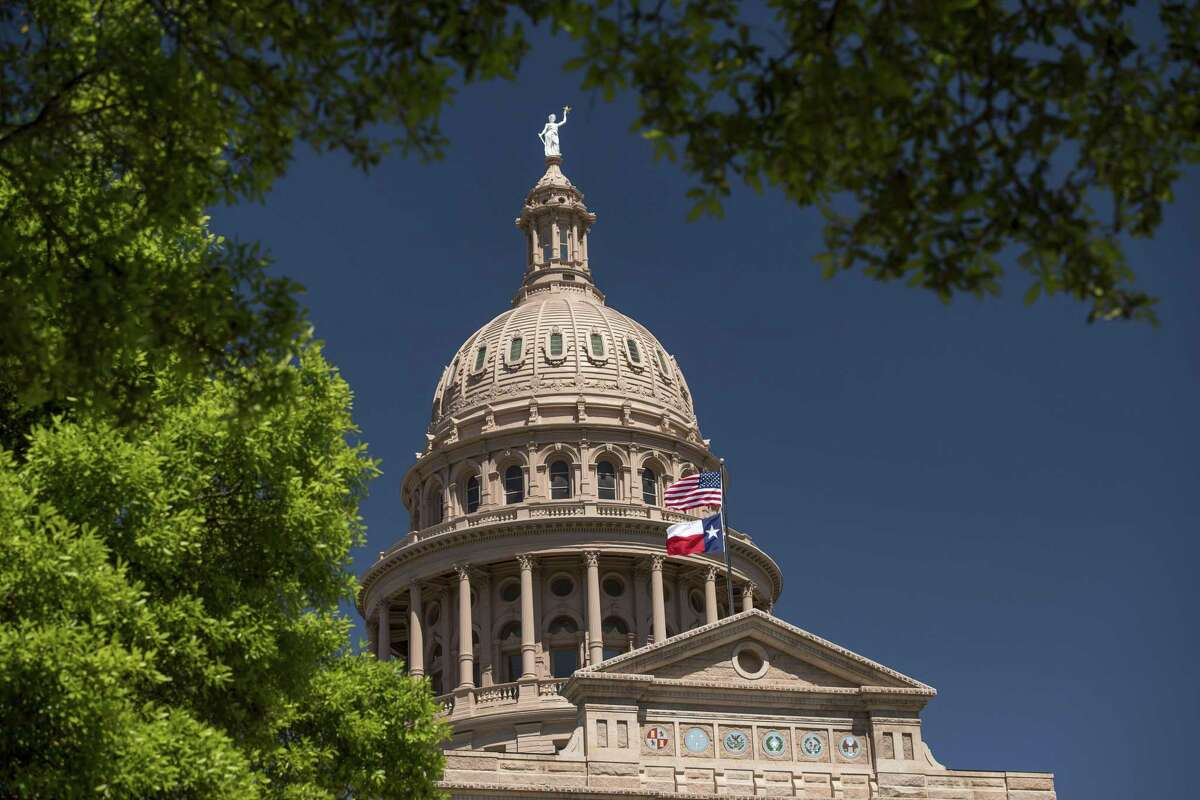 An American flag flies with the Texas state flag outside the Texas State Capitol building in Austin.