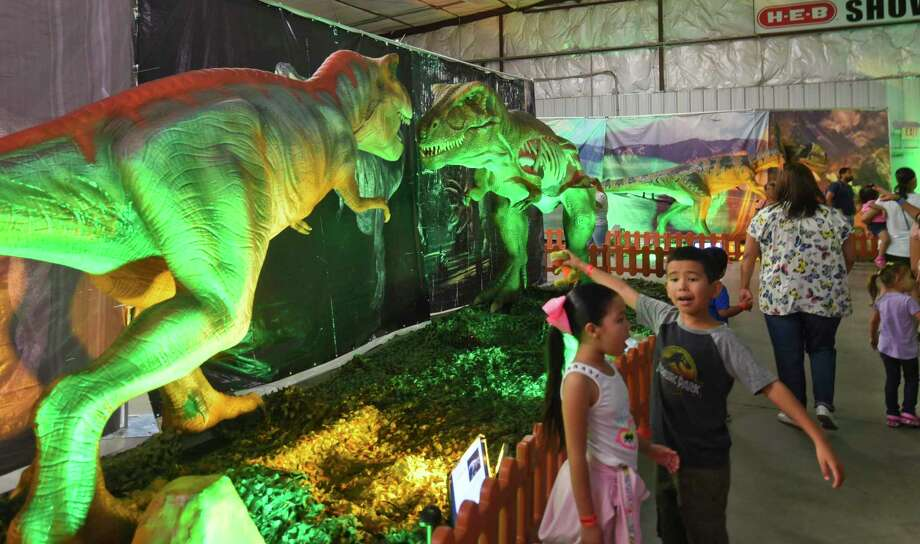 Emily Juarez and Anthony Salazar explore the animatronic dinosaurs at the My Jurassic Adventure display on Saturday at the L.I.F.E. Downs Pavillion. Photo: Danny Zaragoza /Laredo Morning Times / Laredo Morning Times