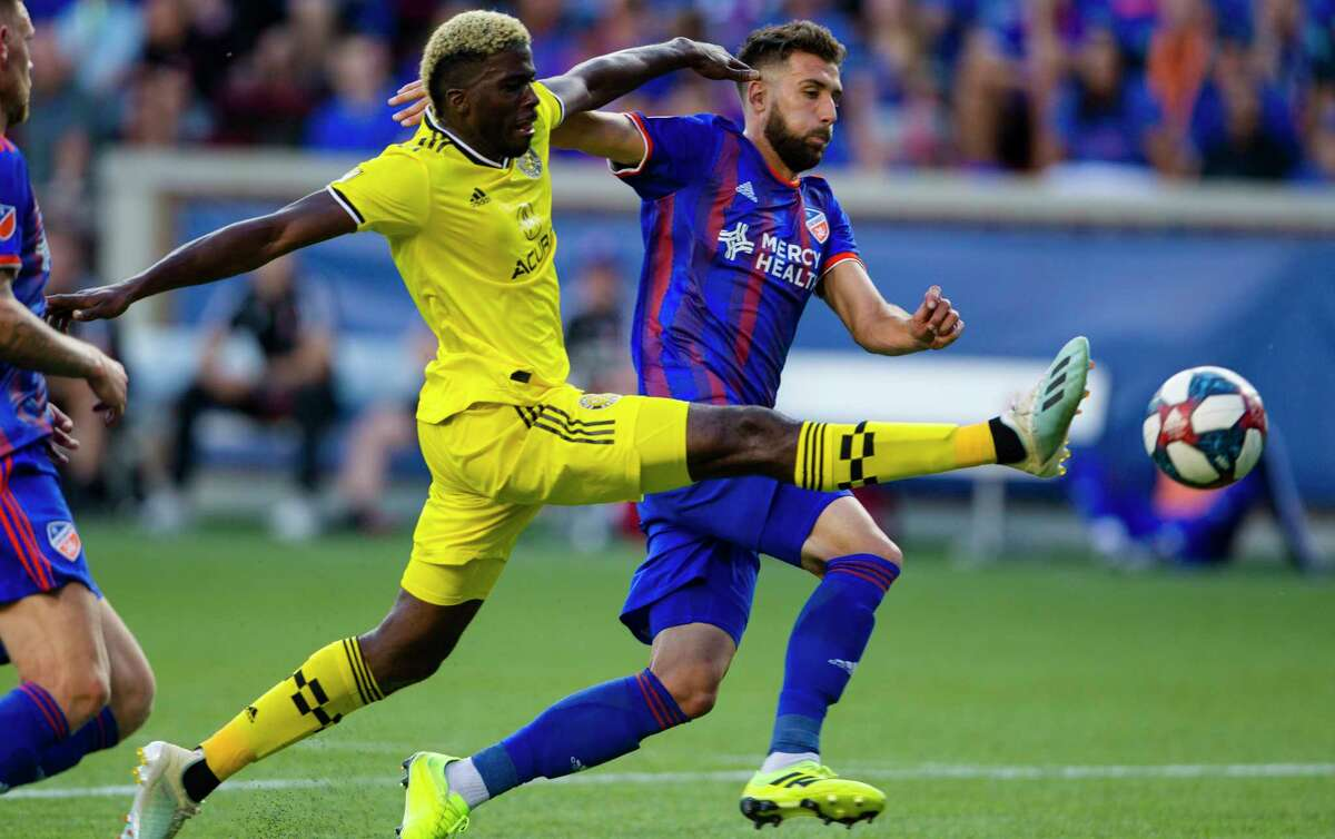 Columbus Crew forward Gyasi Zerdes (11) attempts to shoot on goal as FC Cincinnati defender Mathieu Deplagne (17) defends in the second half of an MLS soccer match on Sunday, Aug. 25, 2019, in Cincinnati. (Albert Cesare/The Cincinnati Enquirer via AP)