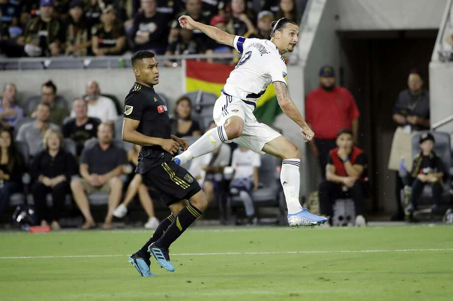 Los Angeles Galaxy's Zlatan Ibrahimovic, right, shoots next to Los Angeles FC's Eddie Segura during the first half of an MLS soccer match Sunday, Aug. 25, 2019, in Los Angeles. (AP Photo/Marcio Jose Sanchez) Photo: Marcio Jose Sanchez / Associated Press
