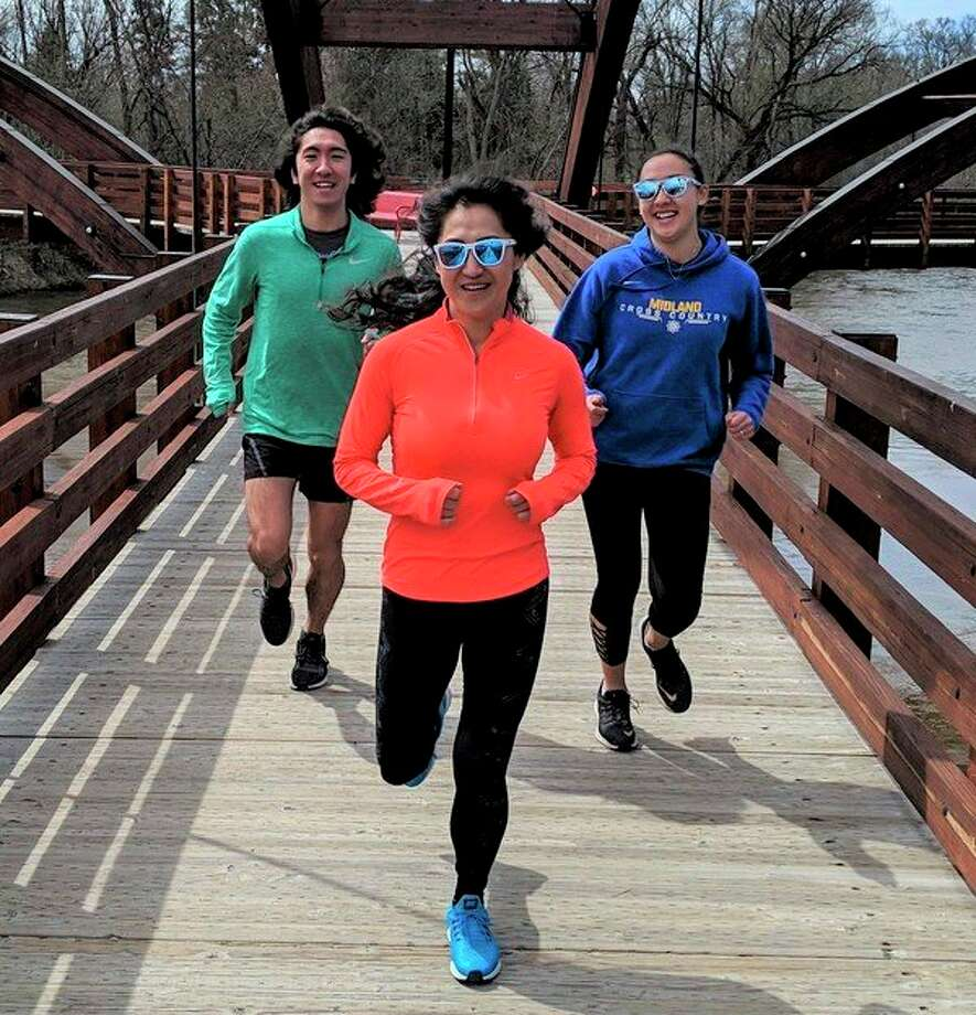 Family Fun on Foot: Jaewon Lim, center, runs with son Hanbyul Johnson, left, and daughter Danbi Johnson at the Tridge this spring. The family belongs to running groups in the Midland area. (Photo provided/Patrick W. Bevier)