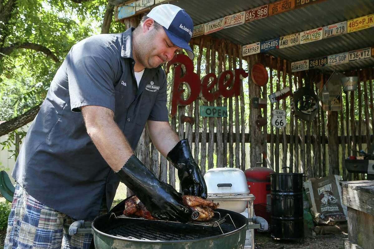 Chuck Blount rotates the Peruvian-style chicken, known for its marinade and flavor, on the grill.