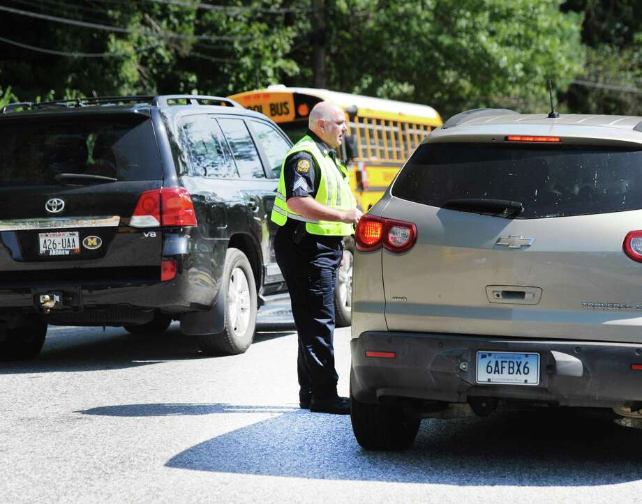 A Greenwich police officer assists a driver on Hillside Road in front of Greenwich High School during dismissal on the first day of school in Greenwich, Conn., Thursday, Agust 30, 2018. Photo: File / Hearst Connecticut Media / Greenwich Time