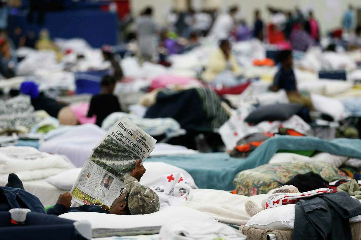 A man reads the Houston Chronicle on a cot at the George R. Brown Convention Center where nearly 10,000 people are taking shelter after Tropical Storm Harvey Wednesday, Aug. 30, 2017 in Houston. ( Michael Ciaglo / Houston Chronicle)