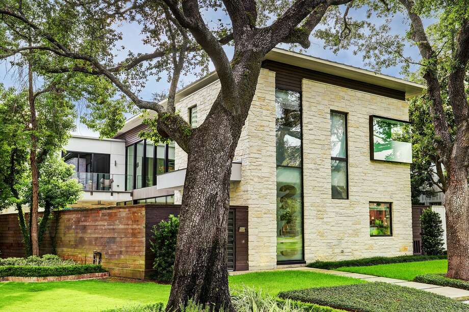 This ultra-modern River Oaks home is set to hit the market next week for a cool $3.5 million, according to Philip Alter of Martha Turner Sotheby's International Realty. Some of the sleek home's stunning amenities include wall-to-wall sliding glass doors that open to a 23-foot lap pool and outdoor patio; a split open-tread staircase that frames a 1,000-gallon saltwater fish tank; a golf simulator and theater room and an AstroTurf backyard and dog run. Photo: Houston Association Of Realtors