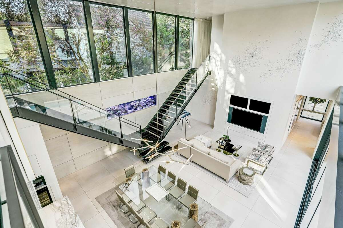 This ultra-modern River Oaks home is set to hit the market next week for a cool $3.5 million, according to Philip Alter of Martha Turner Sotheby's International Realty. Some of the sleek home's stunning amenities include wall-to-wall sliding glass doors that open to a 23-foot lap pool and outdoor patio; a split open-tread staircase that frames a 1,000-gallon saltwater fish tank; a golf simulator and theater room and an AstroTurf backyard and dog run.