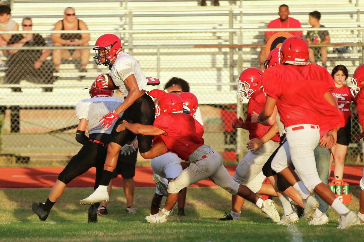 Darvin Lynn hurdles over Cleveland defenders on his way to a big gain for the Coldspring-Oakhurst Trojans in their scrimmage last Friday night at Trojan Field.