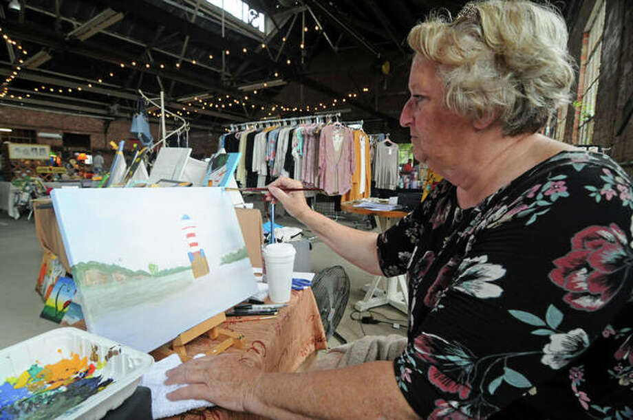 Artist Deborah White of Sidell, Illinois, creates a painting during Sunday's Riverside Flea Market in Grafton. Despite being flooded out in June, the event has recovered and again is seeing good crowds at its monthly events.