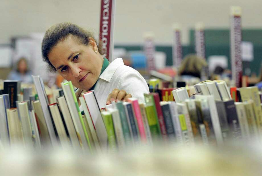Irene Reynolds of Redding, a volunteer at the Mark Twain Booksale, looks over the books Friday, August 31, 2018. Photo: Carol Kaliff / Hearst Connecticut Media / The News-Times