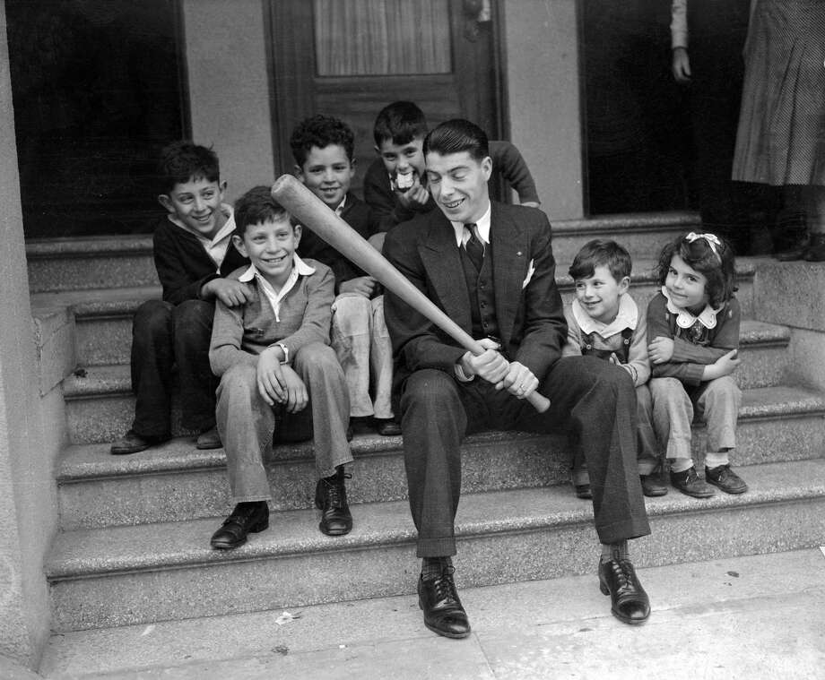 The youngsters of North Beach in San Francisco troop to the DiMaggio home to have Joe DiMaggio, their idol, show them how to clout 'em. Photo: Bettmann/Bettmann Archive