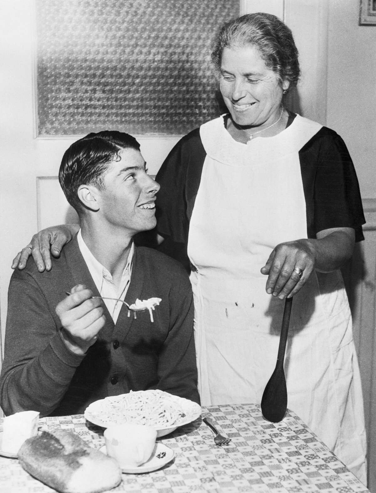 Young Joe DiMaggio eating spaghetti while his mother Rosalialooks on.