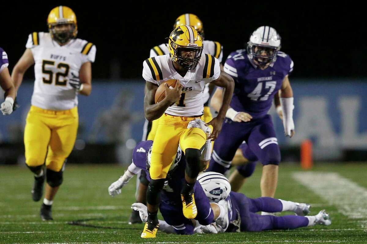 Fort Bend Marshall Buffalos quarterback Malik Hornsby (1) runs through the tackle attempt by Port Neches-Groves Indians Kade Martin (4) in Baytown, TX on Friday, November 30, 2018.