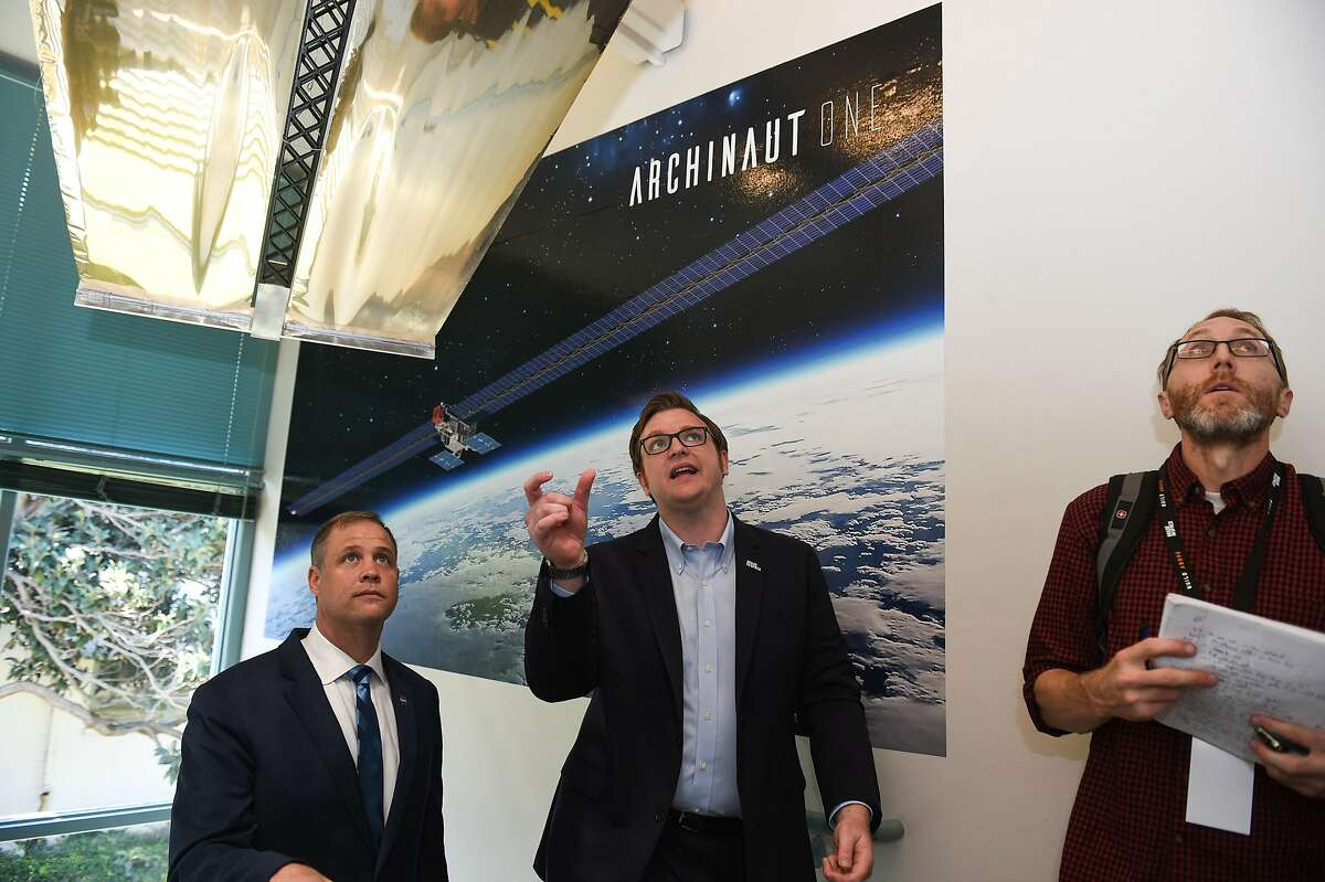 Andrew Rush, President and CEO of Made In Space, center, displays a solar blanket, top, for which the supports can be 3D printed in space, for NASA Administrator Jim Bridenstine, left, in front of a poster for Archinaut One at the Made In Space headquarters on the NASA Ames Research Center in Mountain View on Monday August 26, 2019.