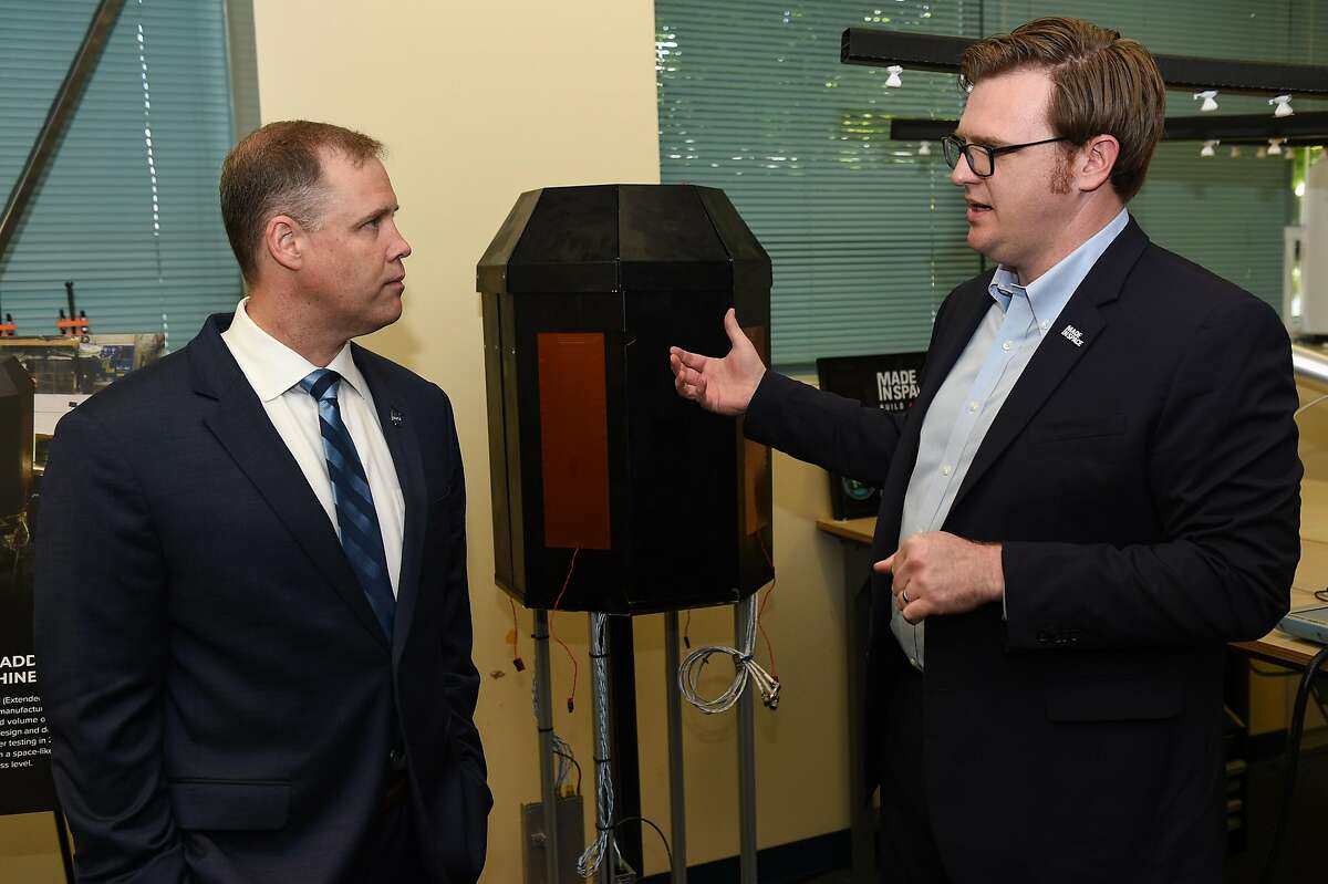 Andrew Rush, President and CEO of Made In Space, right, displays an Extended Structure Additive Manufacturing Machine to NASA Administrator Jim Bridenstine at the Made In Space headquarters on the NASA Ames Research Center in Mountain View on Monday August 26, 2019.