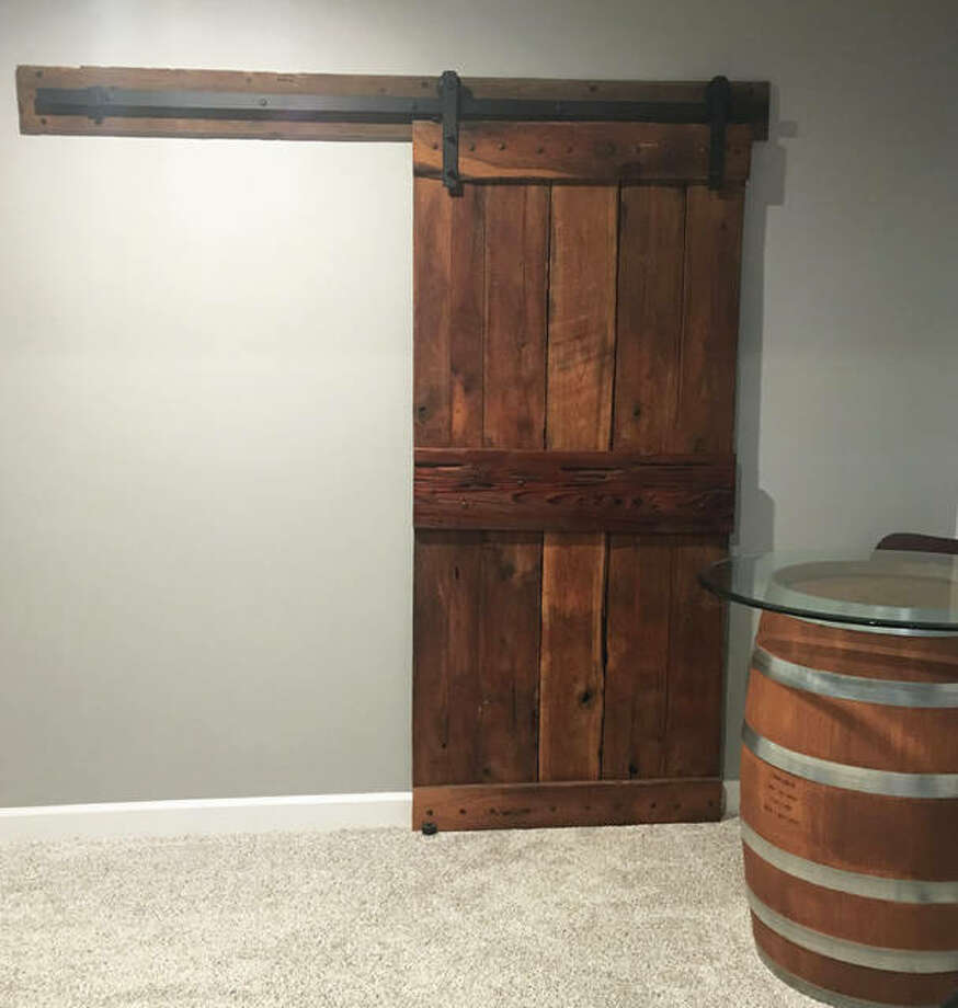 A custom barn door, by B&N Barn Dismantling and Barnwood Sales, hides a storage room in the Rinderers' basement. Photo: Jill Moon|Hearst Illinois