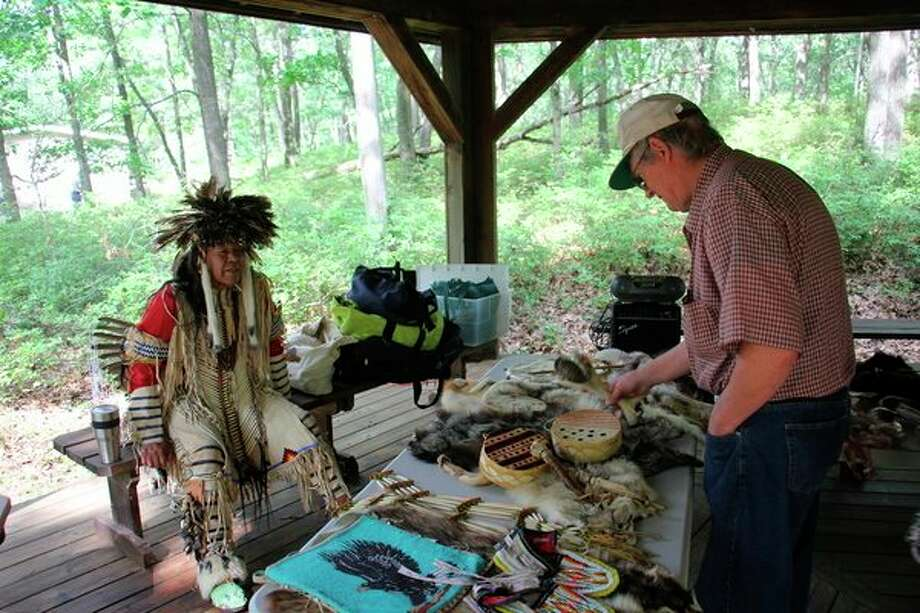 A Native American reenactor talks about tribal accessories at the Three Sisters Festival in Port Austin. The festival showed off aspects of Native American life. (Robert Creenan/Huron Daily Tribune)