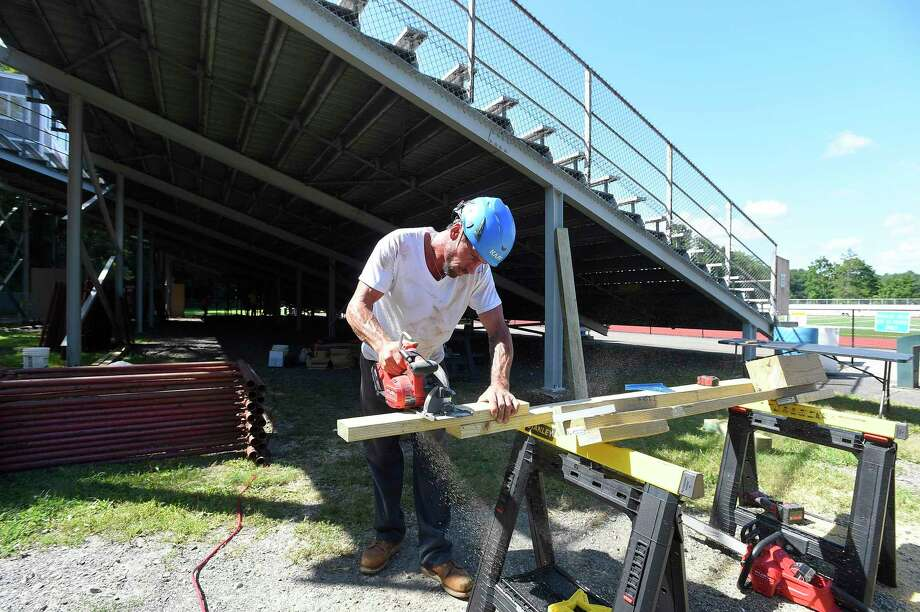 Foreman Brian Dwiight, part of a crew from Veteran's Scaffold and Sevice Inc. out of Blackstone, Massachusetts cuts bracing material as they install temporary structural scaffolding support to the bleachers at Greenwich High School's Cardinal Stadium on August 26, 2016. The Greenwich Athletic Foundation paid $120,000 to rent equipment that would shore up the current bleachers so that they can hold the weight that code requires them to hold; this is a temporary solution while the school district/BOE works on finalizing plans to build new bleachers in their place. Photo: Matthew Brown / Hearst Connecticut Media / Stamford Advocate