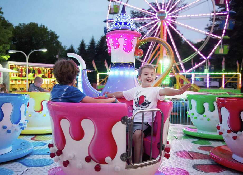 Jack Moskwitz,9, and James Semon,7, ride the teacups at the annual volunteer firemen's carnival Saturday, June 29, 2019 at East Ridge School in Ridgefield, Conn. Jack Moskwitz,9, and James Semon,7, ride the teacups at the annual volunteer firemen's carnival Saturday, June 29, 2019 at East Ridge School in Ridgefield, Conn. Photo: Bryan Haeffele / Hearst Connecticut Media / Ridgefield Press
