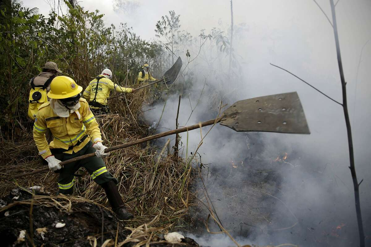 Firefighters work to put out fires along the road to Jacunda National Forest, near the city of Porto Velho in the Vila Nova Samuel region which is part of Brazil's Amazon, Monday, Aug. 26, 2019. The Group of Seven nations on Monday pledged tens of millions of dollars to help Amazon countries fight raging wildfires, even as Brazilian President Jair Bolsonaro accused rich countries of treating the region like a