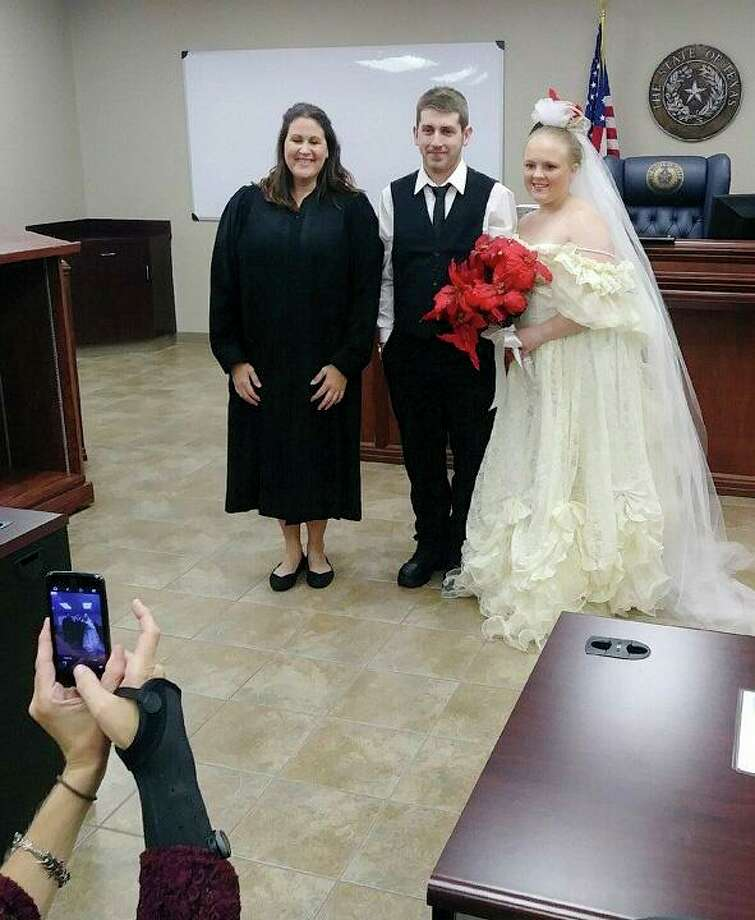 Orange County Justice of the Peace Joy Dubose-Simonton poses with Harley and Rhiannon Morgan after marrying them on Friday. The newlyweds were killed a few minutes later when their car was struck while pulling out of the parking lot onto Texas 87. Photo: Courtesy Photo