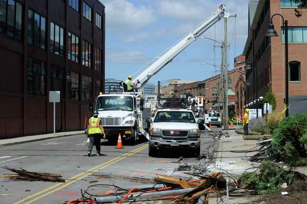 Utility crews from Eversource Power and Frontier Cable work to repair and replace broken utility poles in Stamford.