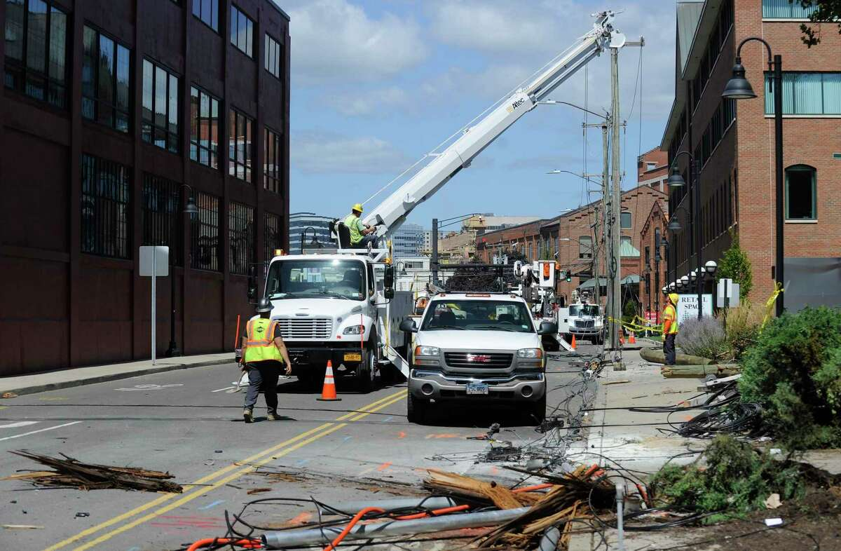 Utility crews from Eversource Power and Frontier Cable work to repair and replace broken utility poles following a car crash in the South End of Stamford along Canal Street resulting in two confirmed fatalities, and four other individuals injured in the morning hours of Monday, August 26, 2016.