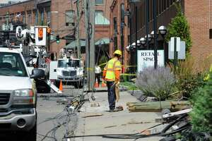 Utility crews from Eversource Power and Frontier Cable work to repair and replace broken utility poles following a car crash in the South End of Stamford along Canal Street resulting in two confirmed fatalities, and four other individuals injured in the morning hours of August 2016.