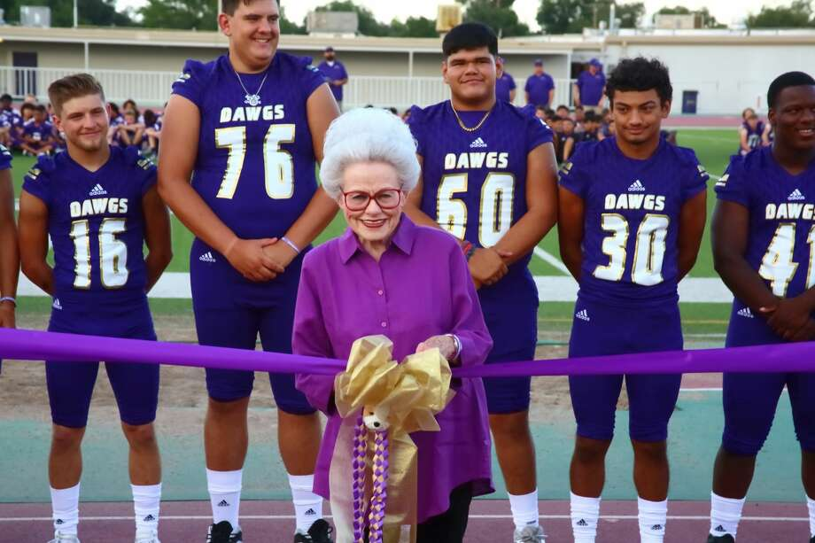 """Gayle Dodson, wife of late athletics trainer James """"Doc"""" Dodson, prepares to cut the ribbon in a dedication ceremony to rename Midland Memorial Stadium to James """"Doc"""" Dodson Memorial Stadium on Saturday night. Behind her are members of the Midland High football team, as it was also """"Meet the Bulldogs"""" night. Photo courtesy of Curtis Routh. Photo: Curtis Routh 