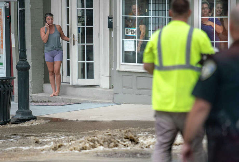 A woman exits River Bend Yoga Studio on State Street Monday evening to discover a torrent of water rushing down the street toward Broadway, as others inside watch from the storefront's windows. Photo: Nathan Woodside | The Telegraph