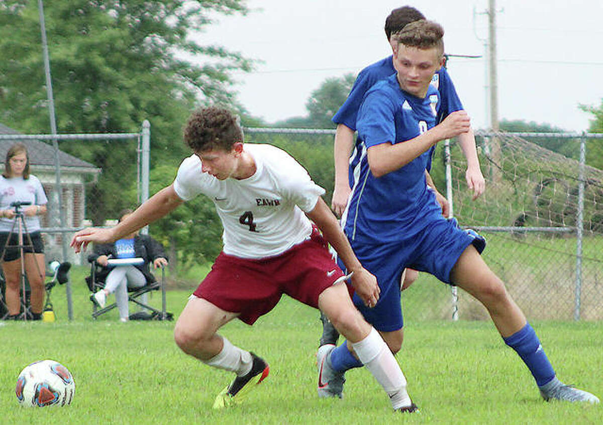 East Alton-Wood river's Ethan Moore, left, goes for the ball along with Carlinville's Kenneth Alepra Monday in the season opener at Loveless Park in Carlinville.