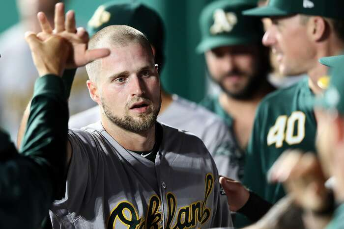 KANSAS CITY, MISSOURI - AUGUST 26: Seth Brown #65 of the Oakland Athletics is congratulated by teammates in the dugout after scoring during the 3rd inning of the game against the Kansas City Royals at Kauffman Stadium on August 26, 2019 in Kansas City, Missouri. (Photo by Jamie Squire/Getty Images)