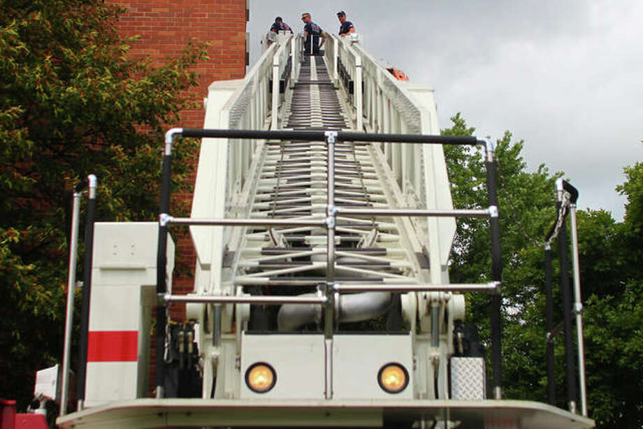 Jacksonville firefighters Logan Griffin, Tom Varns and Ricky Padilla perform ladder truck exercises Monday at Turner High Rise. The training, which involves practice in properly setting up the ladder truck to reach different parts of Jacksonville's taller buildings, happens every two to three years. Photo: Rosalind Essig | Journal-Courier