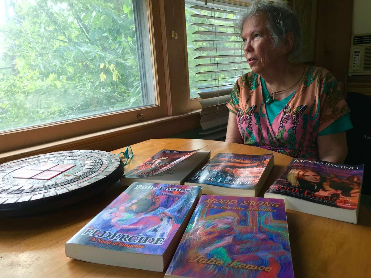 Julie Lomoe, 78, looks out the window of her bungalow above Snyder's Lake, with some of her self-published novels on a table. She created the art on the covers