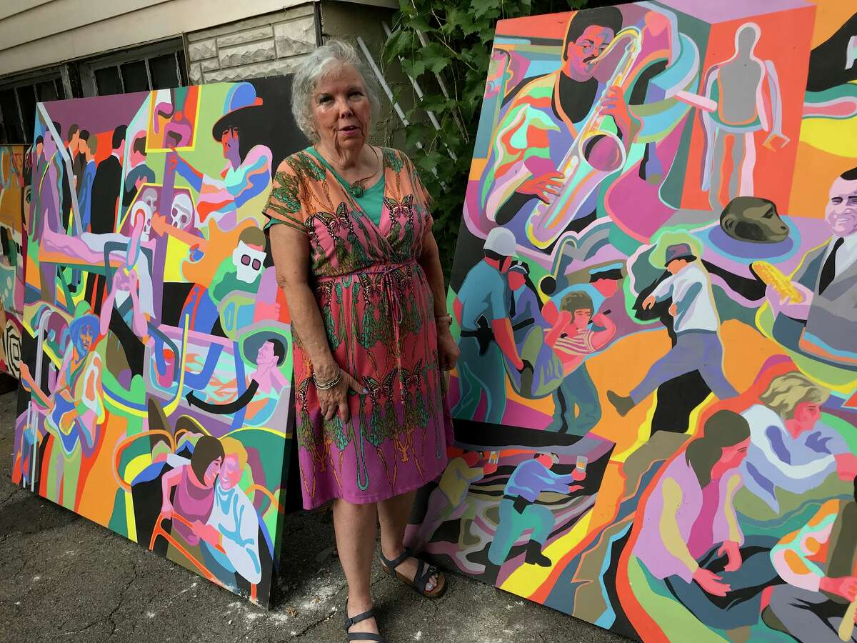 Julie Lomoe poses with two of the large-scale acrylic paintings she brought to the Woodstock Music and Art Festival in Bethel, N.Y. in August, 1969. She won second place, $50 and zero recognition