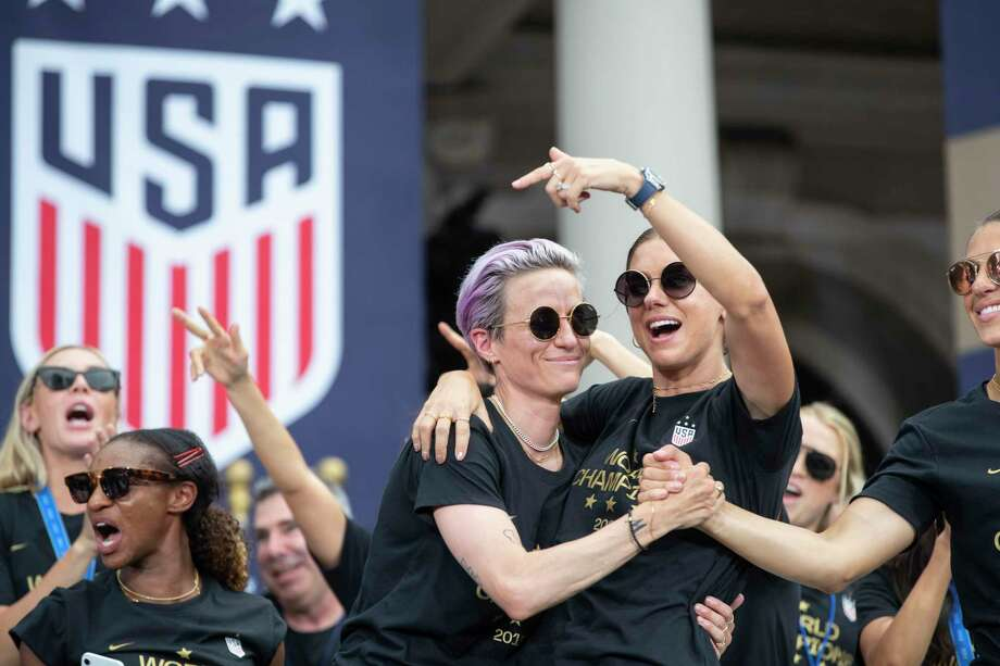 Megan Rapinoe, left, hugs teammate Alex Morgan as they gathered with teammates outside of City Hall, after the team's ticker-tape parade celebrating the U.S. women's national soccer team's World Cup victory, in New York on July 10, 2019. (Calla Kessler/The New York Times) Photo: CALLA KESSLER / NYTNS