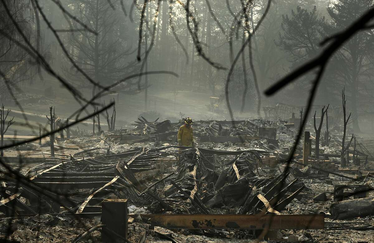 FILE - In this Nov. 16, 2018, file photo, a firefighter searches for human remains in a trailer park destroyed in the Camp Fire in Paradise, Calif. The number of people listed as missing from the deadly Northern California wildfire is down to one after deputies located an Oroville woman. The Butte County Sheriff's Office said Friday, Aug. 2, 2019, that Wendy Carroll was aware she was listed as missing but never contacted authorities because of possible legal issues. The Nov. 8, 2018 Camp Fire killed 85 people. (AP Photo/John Locher, File)