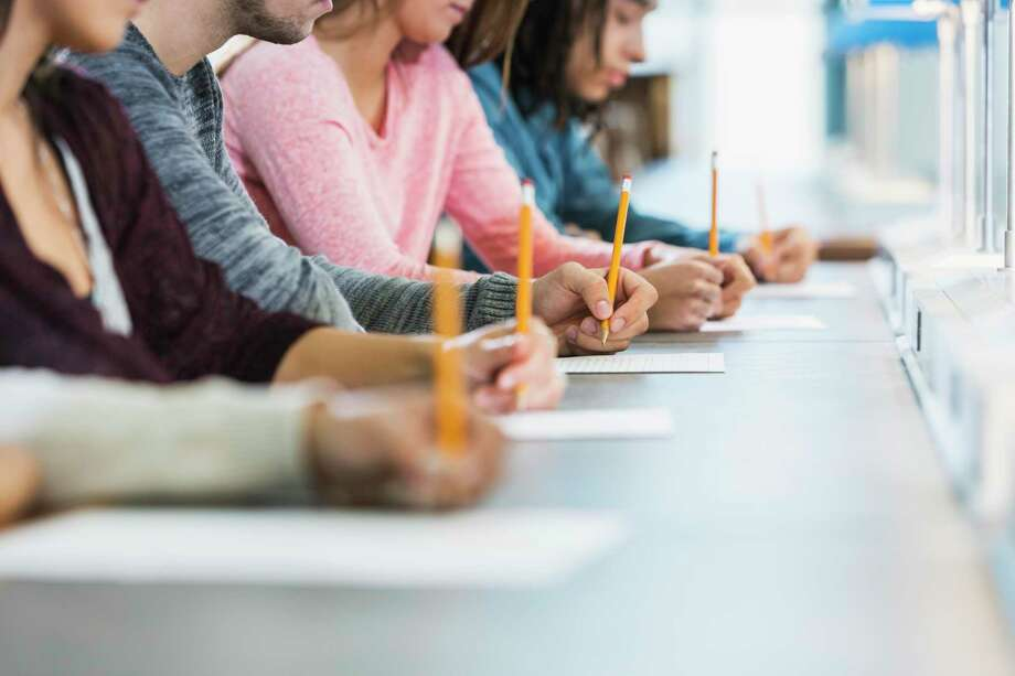 Cropped view of a multiracial group of young men and women sitting in a row at a table, writing with pencils on paper. They are taking a test or filling out an application. Focus is on the hand of the young man in the middle in the gray shirt. Photo: Kali9 / Getty Images / kali9 kali9