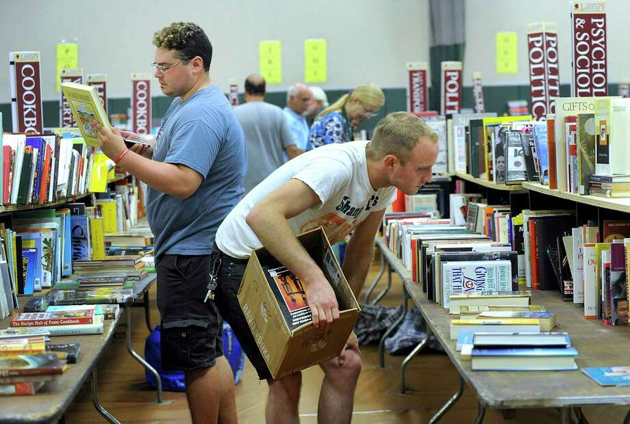 First comers at the opening of the doors to the Redding Community Center Friday morning - mostly dealers and collectors - pour through the thousands of books, vinyl record and other items at the 58th Annual Mark Twain Library Book Fair, August 31, 2018. Photo: Carol Kaliff / Hearst Connecticut Media / The News-Times