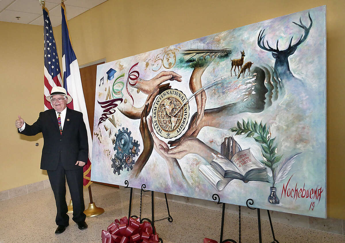Regional artist Arturo Nochebuena Gonzalez poses next to his art work celebrating the 50th Anniversary of Texas A& International University. The work was unveiled following the grand opening of the newest building at the TAMIU Campus, the Academic Innovation Center where it will be displayed.