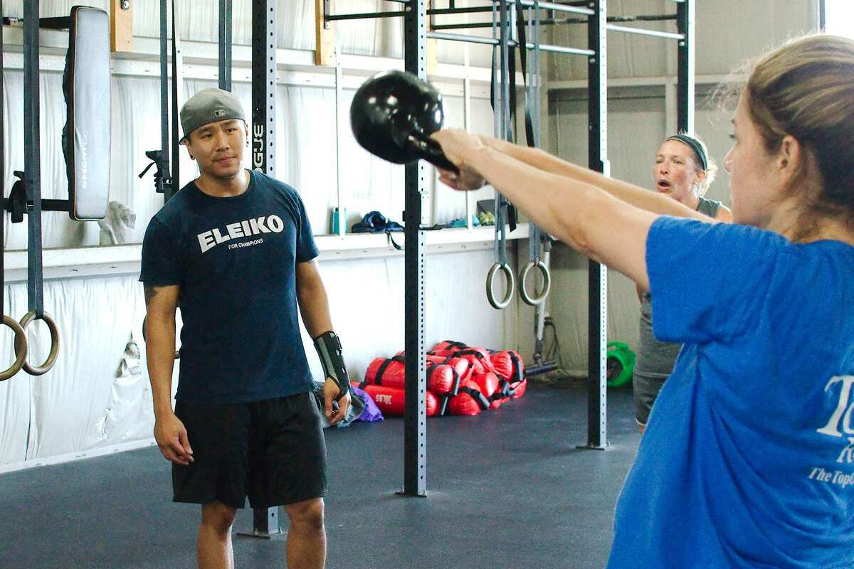 Gym owner Minh Tran observes as clients Jackie Macias and Jessica Ravlin work through fitness routines at Pearland Strength and Conditioning.