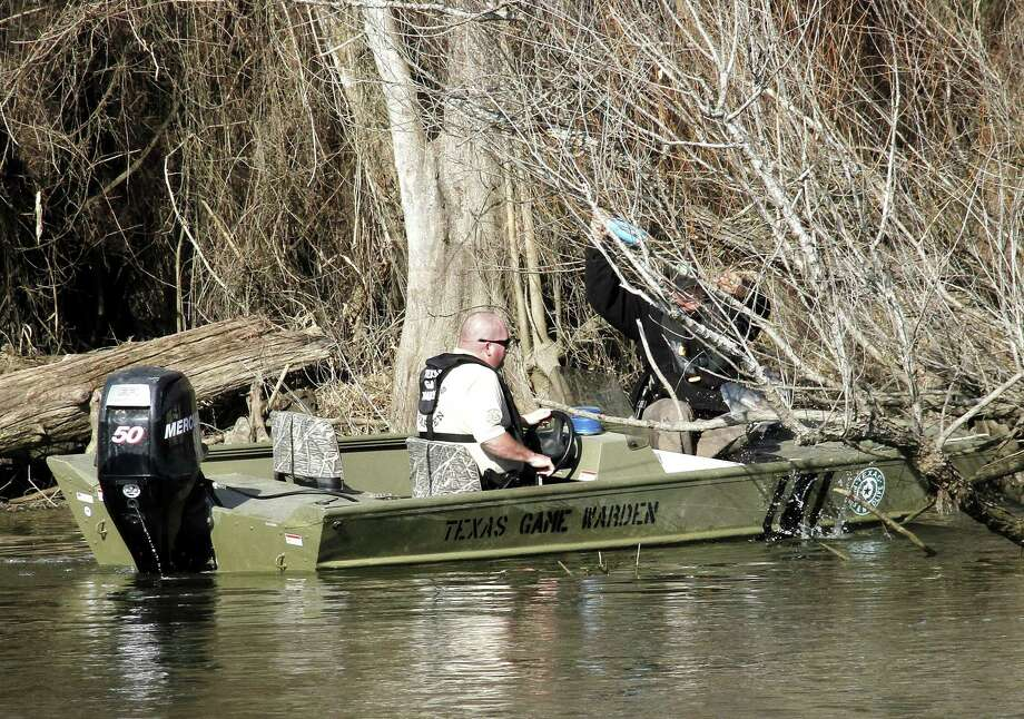 Texas game wardens remove an untagged and abandoned jug line and the catfish it captured from a tangle of willows along a public waterway. Abandoned jug lines, limb lines and trotlines take a toll on freshwater fish and other wildlife as well as posing risks for boaters and anglers and vexing issues for law enforcement. Photo: Shannon Tompkins, Houston Chronicle