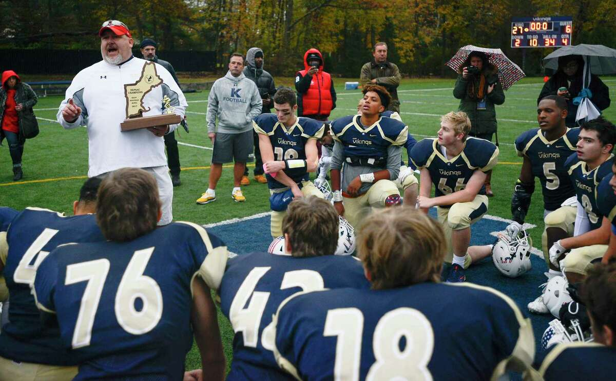 King coach Dan Gouin holds the championship trophy as he talks with his players following the Sean Brennan Bowl of the NEPSAC Class C football championship in Stamford, Conn. on Saturday, Nov. 18, 2017. King defeated Portsmouth Abbey 27-6 to capture their second straight New England football title.
