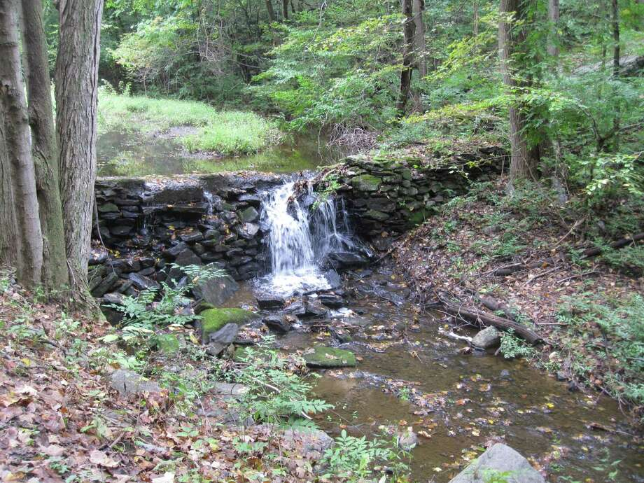 Water spills over a small dam at North Pond in the Grace Richardson Conservation Area. Six people were arrested Aug. 16, 2019 after complaints of lewd conduct in the area. Photo: Contributed Photo / Contributed Photo / Fairfield Citizen contributed