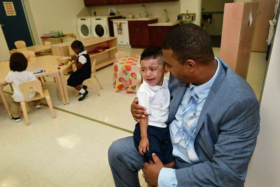 New interim principal James Crouch comforts three-year-old Joseph Criolla as he arrives for the first day of school in one of the new Pre-kindergarten Montessori classrooms at Brookside Elementary School Tuesday, August 27, 2019, in Norwalk, Conn. Photo: Erik Trautmann / Hearst Connecticut Media / Norwalk Hour