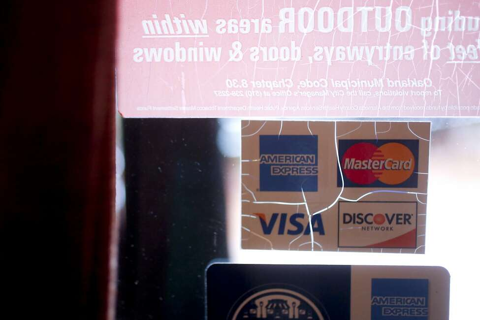 An accepted credit cards sign on the window of a California eatery.