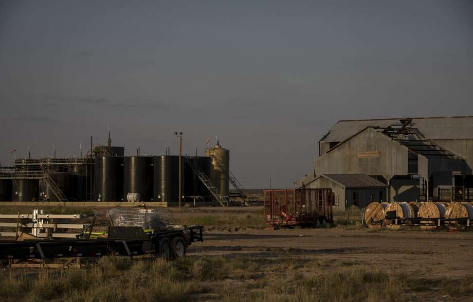 Oil and gas structures sit near an abandoned barn near Balmorhea. Photo: Jon Shapley/Staff Photographer