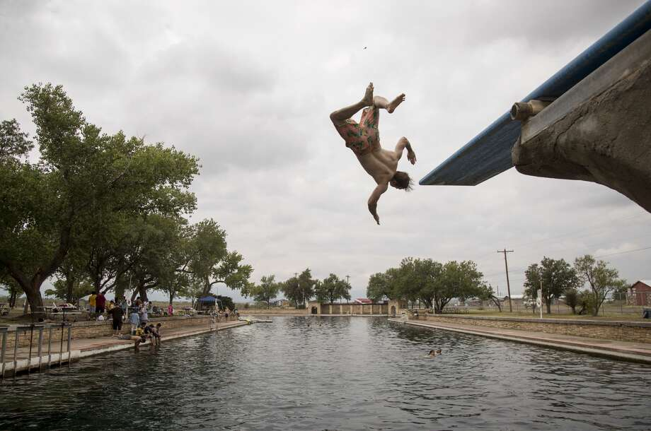 Jeff Nabors, 31, jumps off the diving board at Balmorhea. He said they tried to stay in town but everything was booked. Photo: Jon Shapley/Staff Photographer