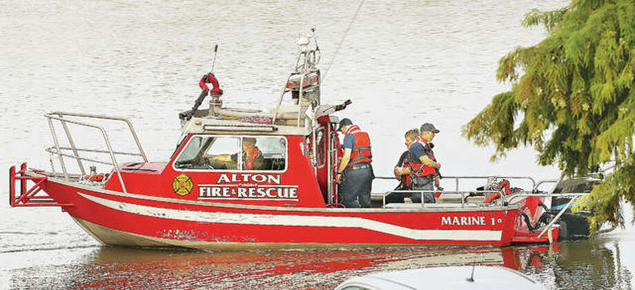 Some of the oncoming shift of Alton firefighters backs Marine 1, the city's fire and rescue boat, out of its slip at Alton Marina to resume searching Tuesday morning for a 41-year-old Alton man who apparently parked the car he was driving on the Clark Bridge about 5:30 a.m. Tuesday and jumped into the Mississippi River. By mid-morning several, agencies were searching for the man who was presumed to have drowned. An officer from the Illinois Department of Natural Resources was aboard a boat from Team Watters Sonar and Recovery in Moro. Photo: John Badman | The Telegraph