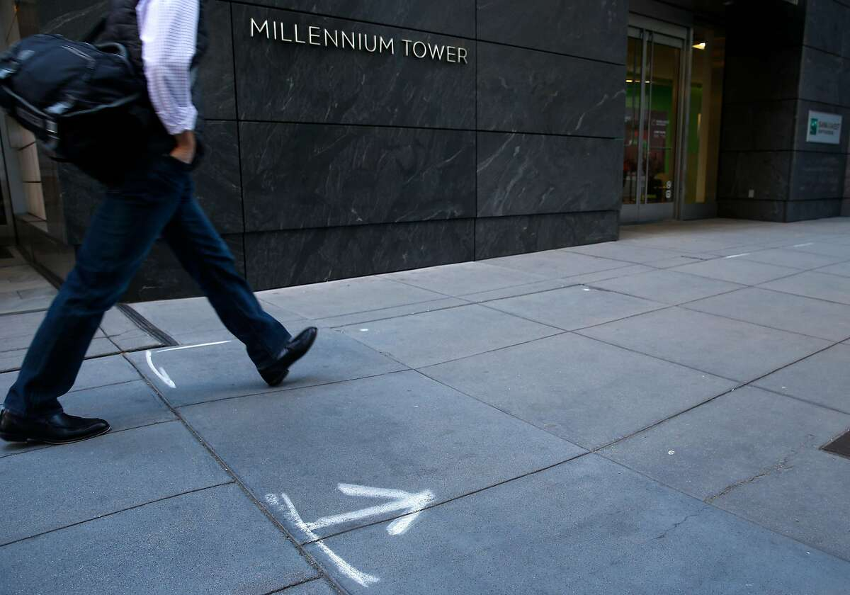 Spray paint marks a section of the sidewalk that sinks and is cracked at the base of the Millennium Tower building on Mission Street in San Francisco, Calif. on Tuesday, March 27, 2018. Engineers may begin preliminary work soon to stabilize the sinking and leaning Millennium Tower.
