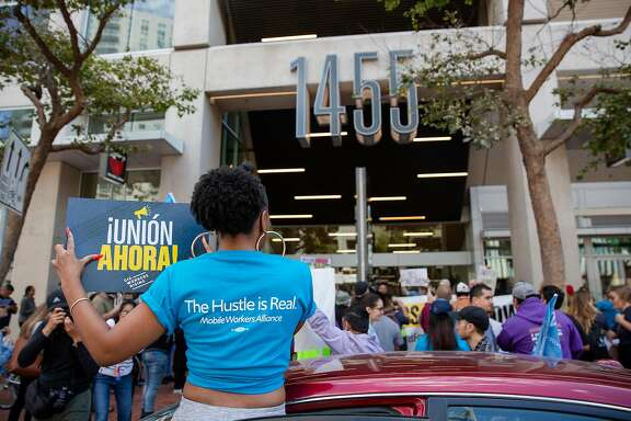 In this photo from August 27, 2019, Uber driver Jessica Porter is holding a sign during a protest in favor of AB5 outside of Uber's Headquarters on Market Street in San Francisco, Calif.